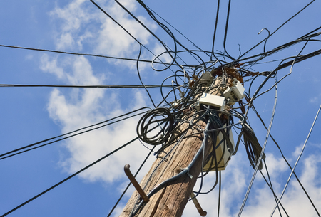 Dangerous mess of electric cables with the sky in the background Stock Photo