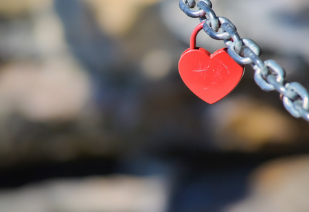 Red padlock in shape of heart hanging on a chain