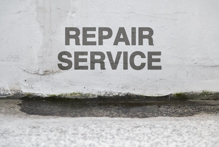 Text Repair Service over a damaged wet wall that needs renovation Stock Photo