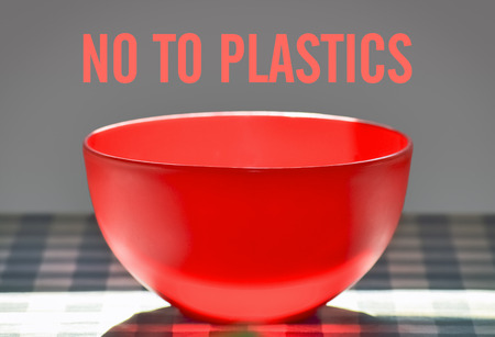 Closeup of a plastic bowl on the table and text No To Plastics