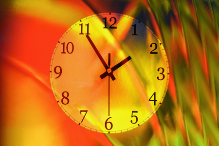 Closeup of a wall clock on a colorful abstract background