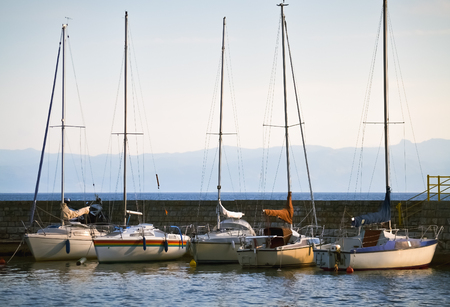 Several small sailboats anchored on a dock in Ohrid lake Stock Photo