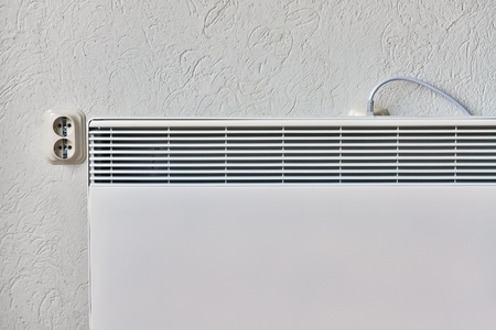 Electrical domestic heater in the room placed near a wall