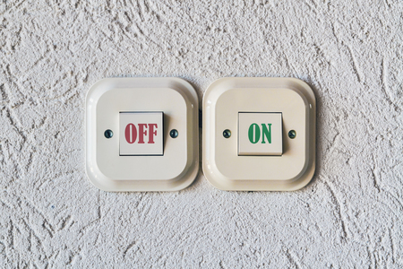 Two electrical switches on the wall with text On and Off on them