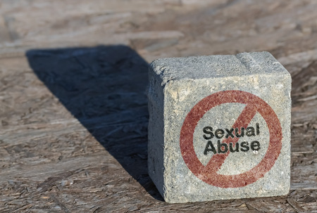 Text Sexual Abuse and restriction sign written on a square stone