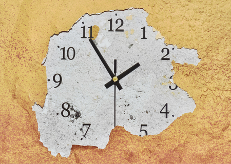 Big clock on a yellow peeling wall showing the time