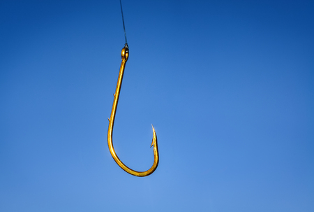 Closeup of a big yellow fishing hook on blue background