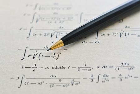 Bleistift über einem Mathematikbuch und fortgeschrittenem Beispiel mit Integralen