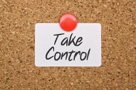 Texte Take Control sur un autocollant épinglé sur un panneau de liège
