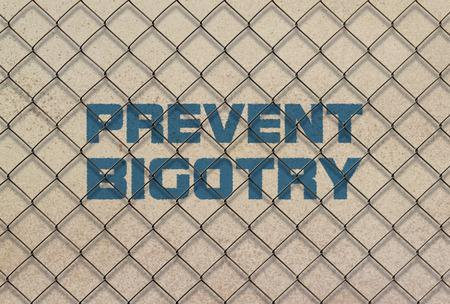 Text Prevent Bigotry written in blue under a wire mesh