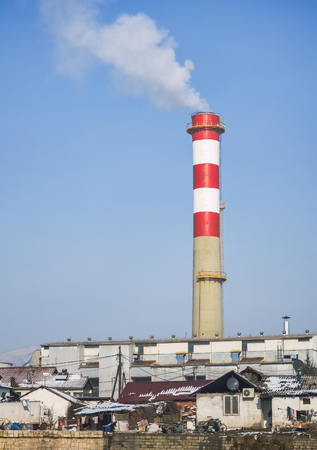 Chimney of a factory exhausting toxic and harmful smoke near a poor suburb Stock Photo