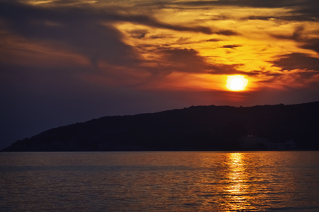 Moody golden sunset over the sea after a hot summer day 写真素材