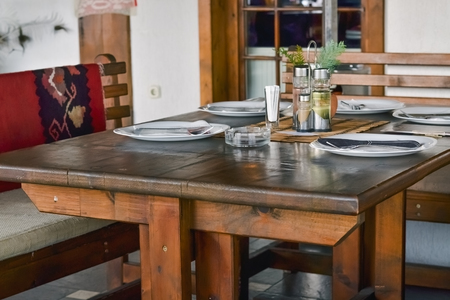 Detail of a restaurant in rustic style with table and chairs made of wood