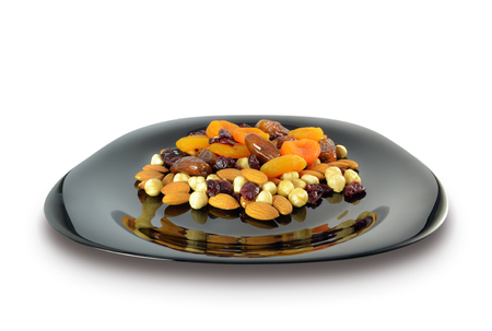 Mix of nuts and dried fruits in a black plate isolated on white background 写真素材