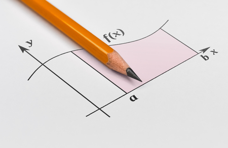 Yellow pencil and graph of a function with shaded area under it Stock Photo