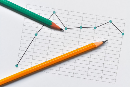 Broken line chart representing the data and two pencils on bright background 写真素材