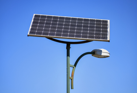 Solar panel and street lamp with clear blue sky in the background