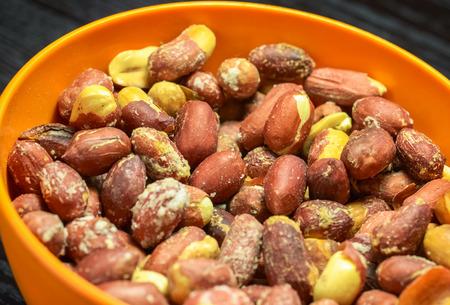 Orange plastic bowl full of roasted peanuts