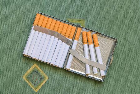Closeup of a metal cigarette case full of cigarettes