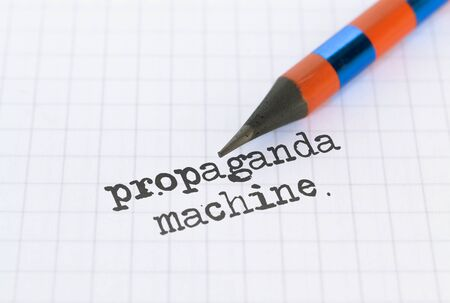 Text Propaganda Machine written on bright background and a pencil