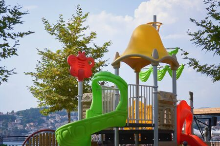 Detail of a colorful playground with plastic toys by the lake