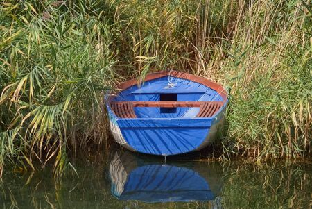 Moored fishing boat floating in the lake and dense reed