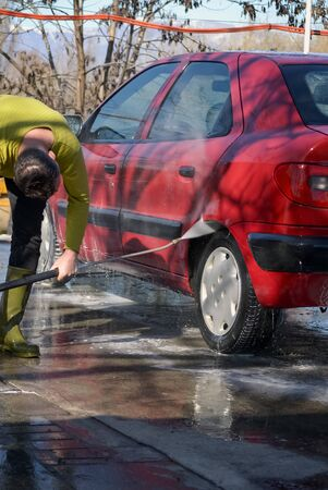 Man washing a car with a high pressure water jet compressor