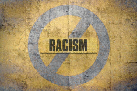 Word Racism written on a grunge yellow background
