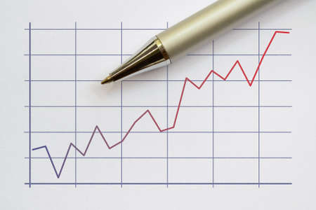 Two color broken line graph and a pen on bright background
