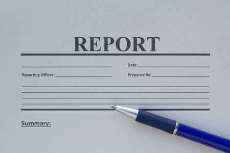 Blank report form printed on paper and a pen