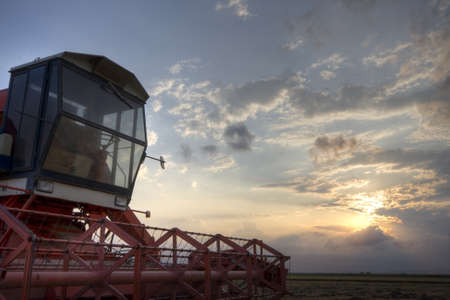 farming tools: Harvester in a rice crop under sunset sky. Valencia (Spain)