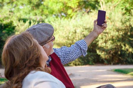 Senior man and senior woman doing a selfie