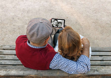A senior man and woman hand using a touchscreen cell phone Stock Photo
