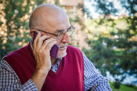 Senior man using cell phone in a park background, Spain. He is 75 years old Stock Photo