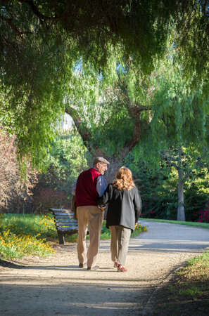 Senior couple walking in the park. They are 75 years old Stock Photo