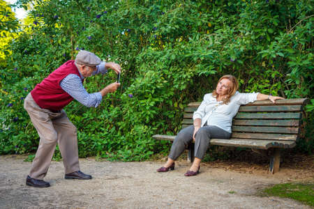 Senior couple in love taking pictures in a park. They are 75 years old
