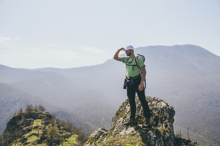 Successful young hiker standing on the top of the mountain and looking around. Stock Photo