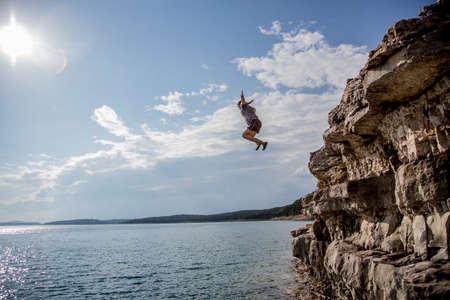 A group of friends jump from cliffs into the lake