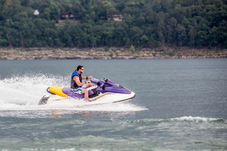 Young man riding jet boat on a summer day at the lake. Stock fotó