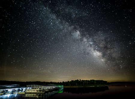 Milky Way reflecting into the lake near a boat dock