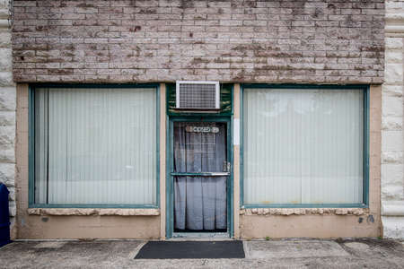 An abandoned store front is empty an neglected with a closed sign on the front door.