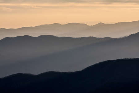 Sun rising over the mountains of Smokies in winter with fog in valleys.