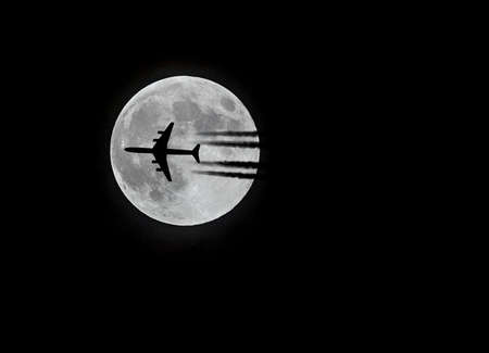 Commercial Airliner passing infront of the moon. Stock fotó