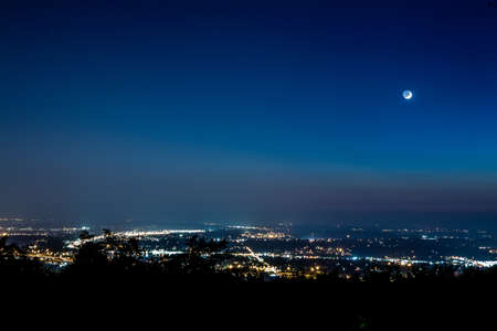 The moon rises over a large metropolitan area.