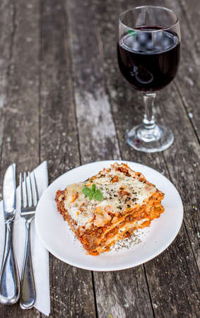 Closeup of a traditional lasagna made with minced beef bolognese sauce topped with basil leafs served on a white plate