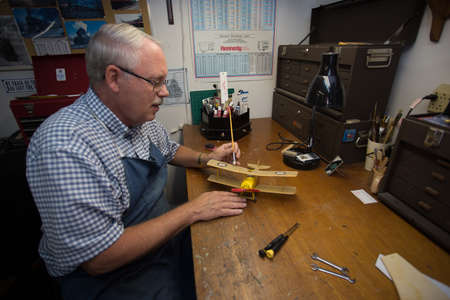 Happy Retired Man working on a model airplane in a shop.