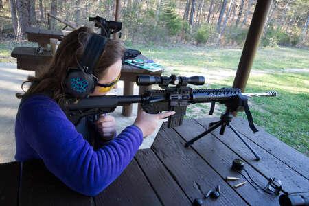 Teenage Girl at shooting range firing an AR-15 rifle.