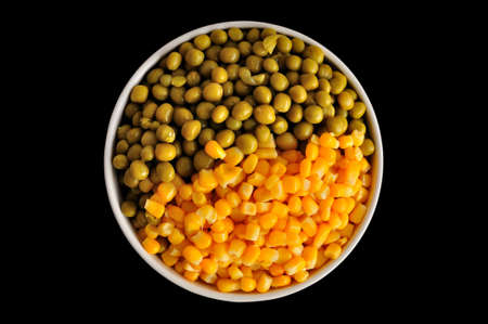 surfeit: a plate with corn and peas, isolated, on a black background Stock Photo