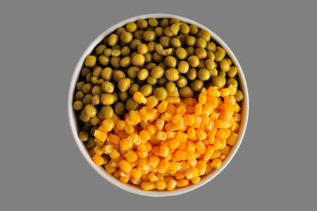 surfeit: a plate with corn and peas, isolated, on a grey background Stock Photo
