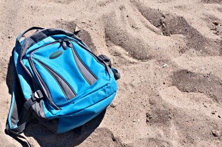trekker: Backpack of blue color on a sandy beach